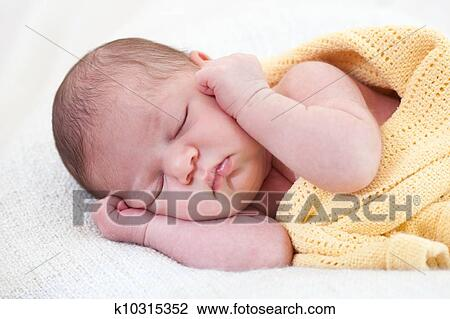 Stock Photo Of Sleeping Newborn Baby Wrapped In A Yellow Blanket