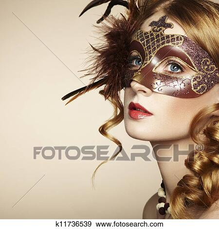 e55e5f4c0d8ab Stock Photo - Beautiful young woman in brown mysterious venetian mask .  Fotosearch
