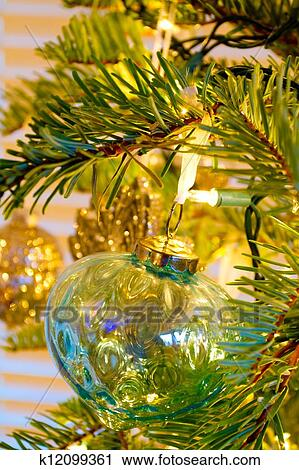 elegant beautiful christmas tree ornaments hang from this fir with lights and decorations all around - Elegant Christmas Ornaments