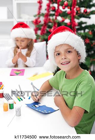 Stock photography of kids making christmas greeting cards k11734500 kids making christmas and seasonal greeting cards in front of the decorated tree m4hsunfo