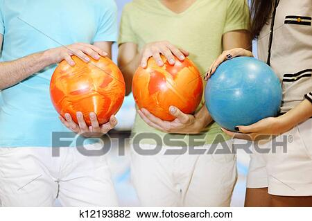 Hands Of Two Men And Woman Make Row From Orange And Blue Balls In Bowling Club Shallow Depth Of Field