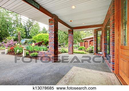 House Front Covered Porch With Wood Door And Spring Landscape