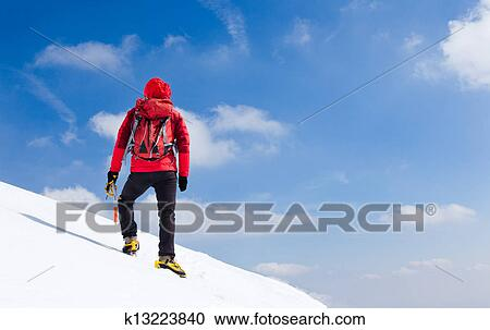 Mountaineer walking uphill along a snowy slope. Stock ...