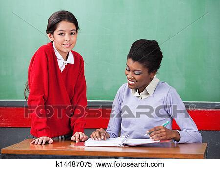 Portrait Of Cute Little Schoolgirl With Teacher Reading Binder At Desk In Classroom