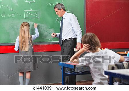 Rear View Of Little Schoolgirl Writing With Teacher Standing By Board In Classroom