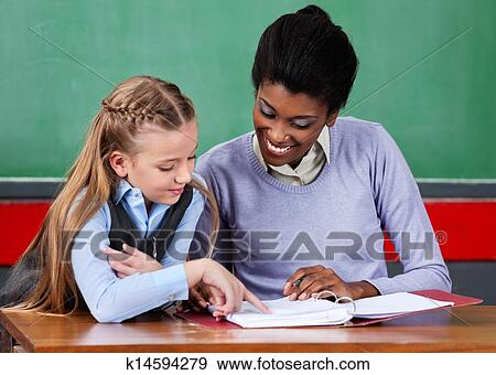 Stock Photograph Teacher Assisting Schoolgirl At Desk Fotosearch Search Stock Photography Posters