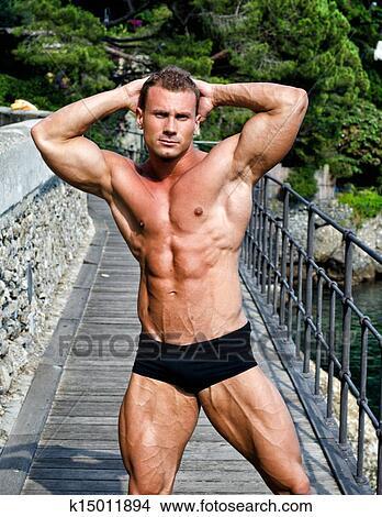 https://fscomps.fotosearch.com/compc/CSP/CSP993/beau-jeune-homme-muscle-dehors-image__k15011894.jpg