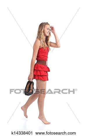 170a2ee4a Beautiful teen girl wearing dress walking with heels hanging from her hand  isolated on a white background