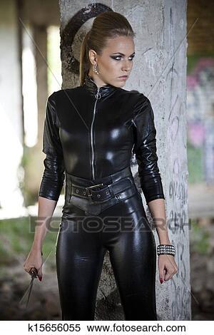 Frau In Leder Kleid Mit Messer Stock Fotografie