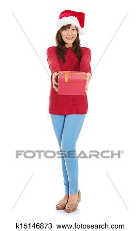 ec65a6cae2df6 Christmas woman holding gift wearing Santa hat. Standing in full body  isolated on white background. Smiling woman portrait of a beautiful Asian  model.