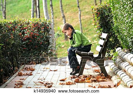 stock photography of sad boy sitting alone on a bench in a way