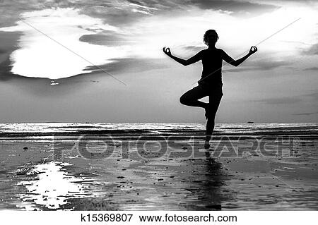Picture Of Young Woman Practicing Yoga On The Beach At Sunset Black