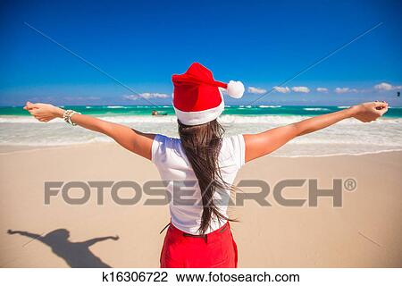2e10efca132 Back view of beautiful girl in Santa Hat walking spread her hands on white  beach
