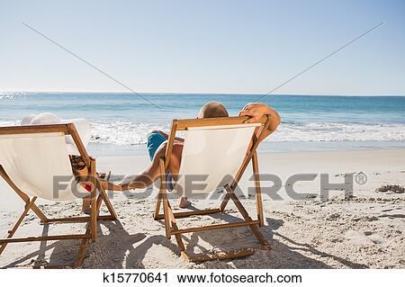 Cute On The Beach Lying Their Deck Chairs