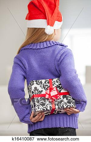 96c9b83d0e6 Rear view of girl in Santa hat hiding Christmas gift behind back at home