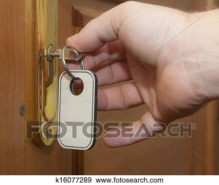 stock photograph of hand with keys unlocking the front door