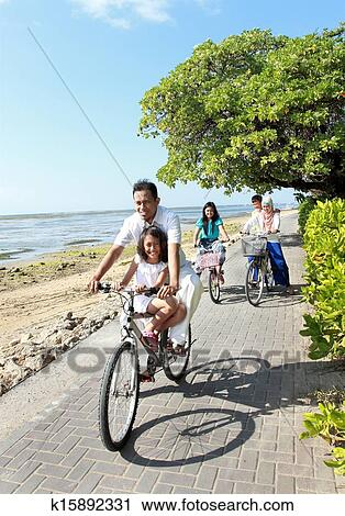 Hy Asian Family Riding Bikes In The Beautiful Morning At Beach Outdoor Portrait