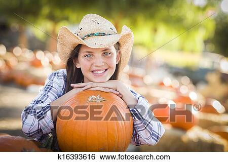 7a4b7f2575c Portrait of Preteen Girl Wearing Cowboy Hat Playing at the Pumpkin Patch in  a Rustic Country Setting.