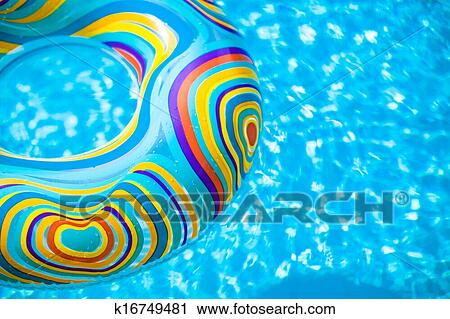 Inflatable colorful Rubber Ring floating in blue swimming ...