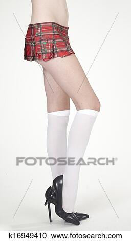 a3192e5089 Close up of woman's legs in plaid school girl skirt, white socks, and black  heels against a white studio background