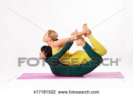 senior and younger woman practice yoga stock image