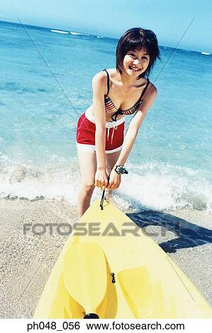 stock images of young woman pulling sea kayak into water ph048 056