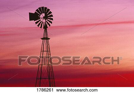 stock photography of windmill silhouette against coloured sky