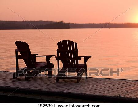 Lake Of The Woods, Ontario, Canada, Adirondack Chairs On A Dock Facing The  Sunset