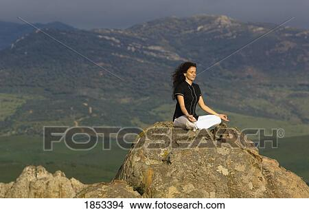 woman in yoga pose on mountain top boulder picture