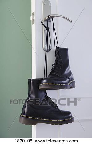 A pair of black boots tied together by the laces and hanging from a  doorknob Stock Photography