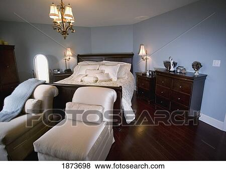 A Bedroom With Chaise Lounge Chairs At The Foot Of The Bed Stock Photo 1873698 Fotosearch