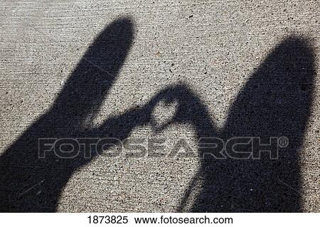 Stock Image of shadow of two people shaping a heart with their hands ... 27cf4404c9