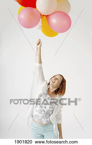 stock photography of a woman holding a bunch of helium balloons