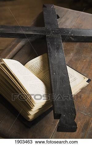 stock photo of black wooden cross on top of an opened bible