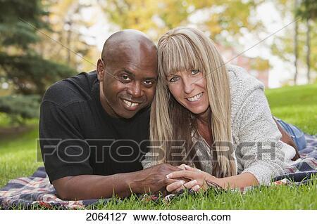 Interracial Couple Cuddling On A Blanket In Park Edmonton Alberta Canada