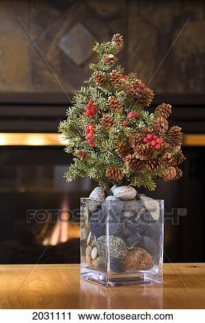 Small Real Fur Tree Decorated With Cones And Red Berries Christmas On A Table In Glass Vase Filled Round Stones Glowing Firplace The