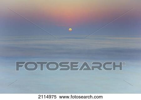 134f871624 Sun rising over blurred water; spain Stock Photography