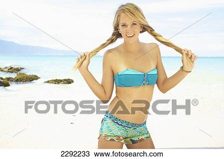 7c19de84fb Stock Image - A teenage girl on a beach wearing a two piece bathing suit  holding