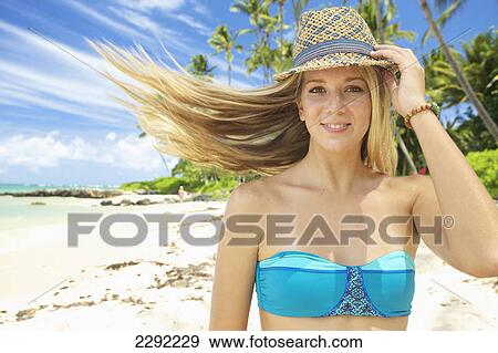 820279fff6 A teenage girl on the beach in a two piece bathing suit and hat with her  long hair blowing in the wind; Maui hawaii united states of america Stock  Photo