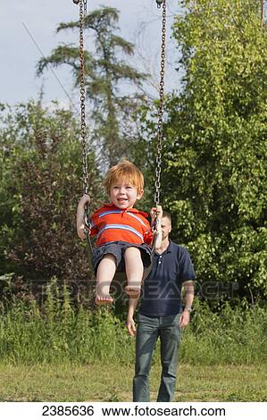 Stock Images Of A Boy Swinging On A Swing Set With His Father In The