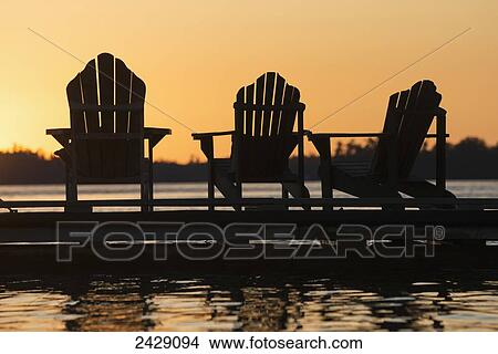 Silhouette Of Three Adirondack Chairs On A Dock At Sunset; Ontario, Canada