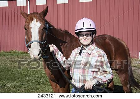 stock photography of a young woman posing with her horse