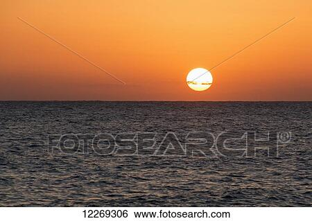 ff76805c34 Glowing sun over the ocean and horizon at sunset; Paphos, Cyprus Stock  Photograph