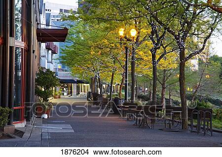 stock photo of tables and chairs along a walkway in the city