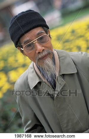 32d0d3630a Vietnam, retrato, de, hombre, con, barba, y, flores amarillas, en,  background;, hanoi