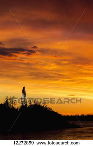 Silhouette of an old wooden drilling rig on tree covered hillside with  dramatically colourful clouds at sunrise