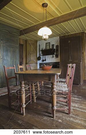 Antique Wooden Dining Table And Chairs In The Kitchen Of An Old Canadiana  (Circa 1840) Cottage Style Residential Fieldstone Home, Quebec, Canada.  This ...