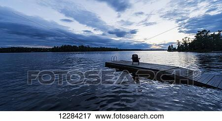 Silhouette of an adirondack chair on a wooden dock along a lake at sunset;  Ontario, Canada Stock Photo