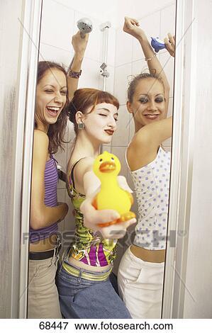 Side Profile Of Three Teenage Girls Having Fun In Bathroom Stock Photo