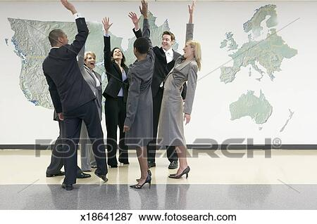 Picture of business people standing in circle cheering and raising business people standing in circle cheering and raising hands in office with world map on wall gumiabroncs Gallery